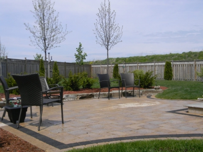 Backyard with natural stone, plantings and interlock patio