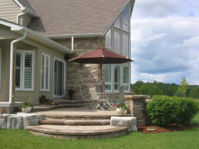 Raised patio with pillars and natural stone and burning bush hedge