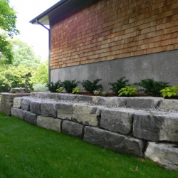 Limestone retaining wall along side of house
