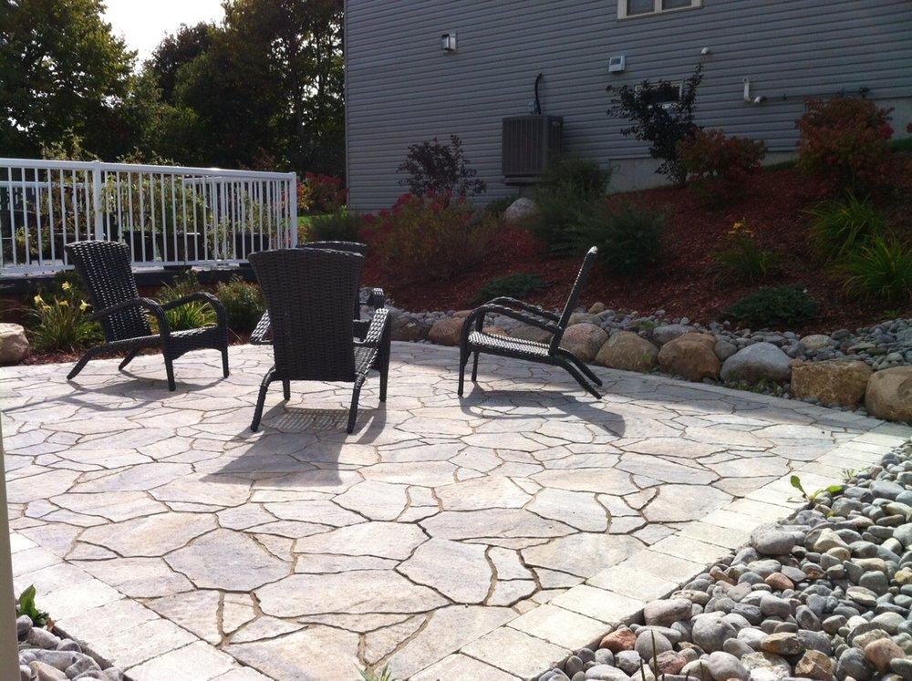 Mega Arbel patio with furniture, granite boulders and river rock